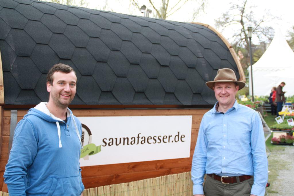 Das Saunafass Team steht vor einer Fasssauna.