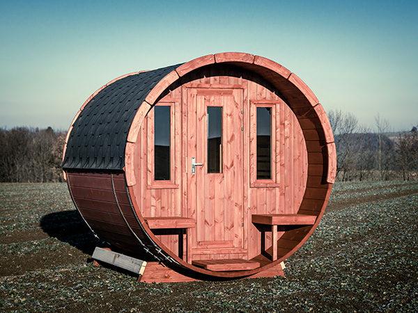 Unser Saunafass Premium 280 steht auf einem Feld.